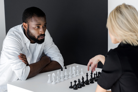african american boyfriend and blonde girlfriend playing chess, yin yang concept Banco de Imagens