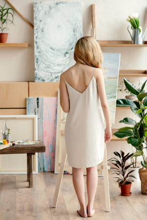 back view of tender young barefoot woman standing near easel in art studio Stok Fotoğraf
