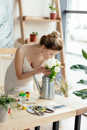 beautiful young woman sniffing flowers in watering can in art studio