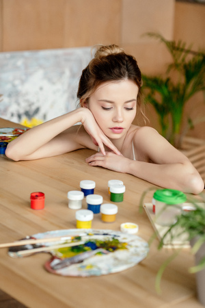 beautiful tender young artist leaning at table with paints and palette