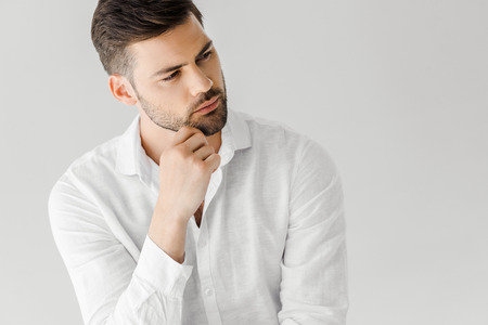 portrait of thoughtful man in linen white shirt looking away isolated on grey background Imagens