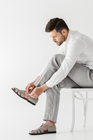 side view of man in linen clothes sitting on chair and putting on sandals isolated on grey background