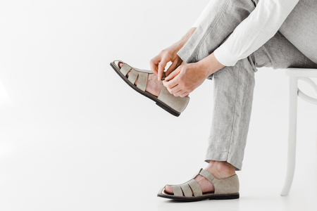 cropped image of male model in linen trousers sitting on chair and putting on sandals isolated on grey background