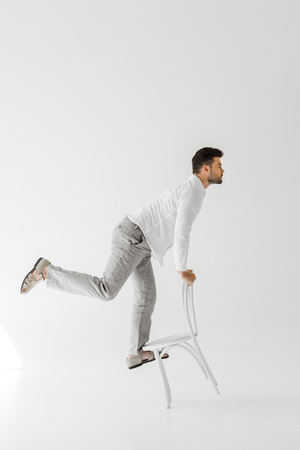 side view of man in linen clothes balancing on chair isolated on grey background Reklamní fotografie