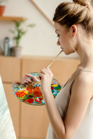 side view of attractive young artist with palette and brush painting on easel in studio Stok Fotoğraf