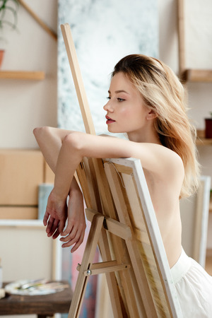 beautiful pensive naked artist leaning at easel and looking away in art studio