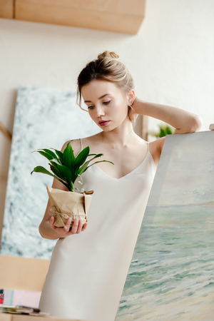 beautiful young artist leaning at picture on easel and looking at green potted plant