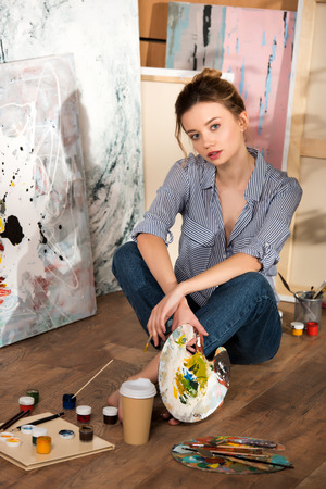 beautiful young artist sitting on floor and looking at camera in art studio Stok Fotoğraf