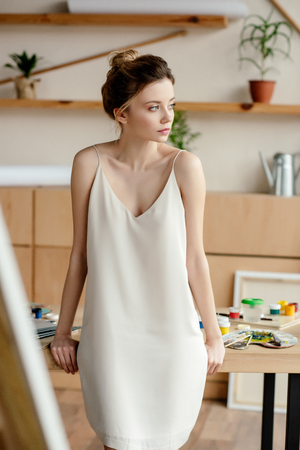 beautiful tender young artist sitting on table and looking away in art studio