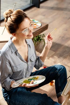 smiling stylish female artist in eyeglasses holding palette and paintbrush Stok Fotoğraf