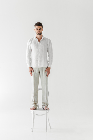 handsome man in linen clothes standing on chair isolated on grey background