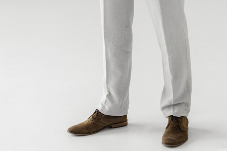 cropped image of male model in linen trousers and suede shoes isolated on grey background
