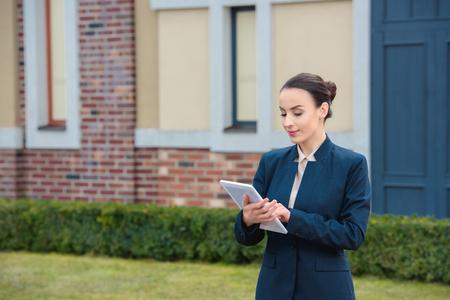 beautiful businesswoman using tablet on street