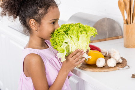african american child sniffing green lettuce in kitchen Banco de Imagens
