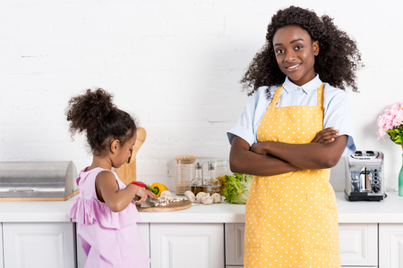 african american mom standing with crossed arms while daughter cutting vegetables on kitchen Banco de Imagens