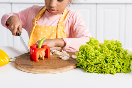 cropped view of african american kid in apron cutting vegetables on wooden board in kitchen