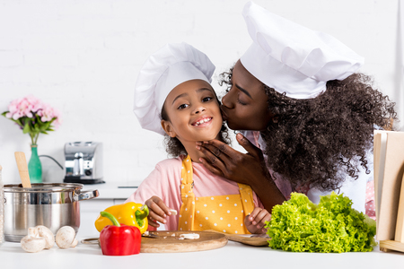 african american mother kissing her daughter in chef hat while cooking on kitchen