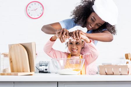 Smiling African American mère et fille dans des chapeaux de chef mettant des oeufs dans un bol ensemble sur la cuisine