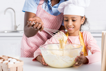 african american mother and daughter in chef hat making dough on kitchen Banco de Imagens