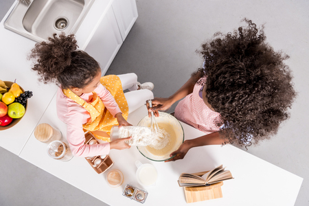 overhead view of african american mother and curly daughter making dough in bowl on kitchen