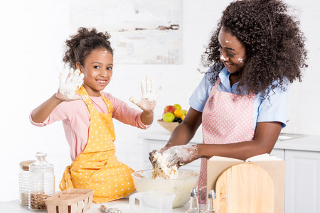 smiling african american mother and daughter kneading dough in bowl on kitchen Banco de Imagens