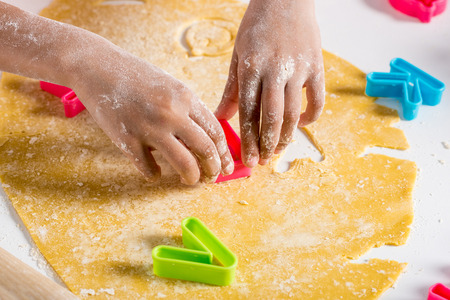 partial view of african american kid making cookies with letters cutters