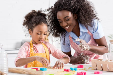 happy african american mother and daughter making cookies with cookie cutters together on kitchen