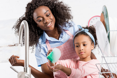 happy african american mother and daughter washing dishes with sponge and foam on kitchen Reklamní fotografie