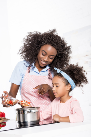 smiling african american mother and daughter putting ingredientes in saucepan on kitchen 写真素材