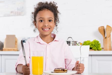 cheerful african american kid having pancakes and orange juice for breakfast