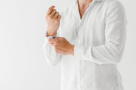 beschnittenes Bild des Mannes im weißen Leinenhemd lokalisiert auf grauem Hintergrund