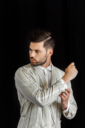 handsome young man in stylish striped jacket buttoning sleeve isolated on black