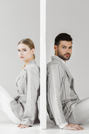 side view of couple of models in stylish jackets leaning back on sides of wall on white and looking at camera Stock Photo