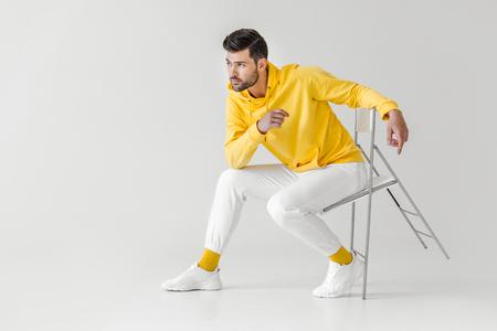 stilvoller junger Mann im gelben Kapuzenpulli, der auf Stuhl auf Weiß sitzt