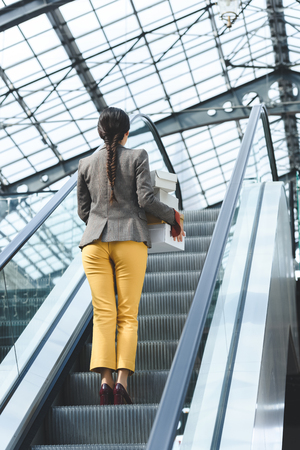 back view of woman standing with shopping boxes on escalator in mall