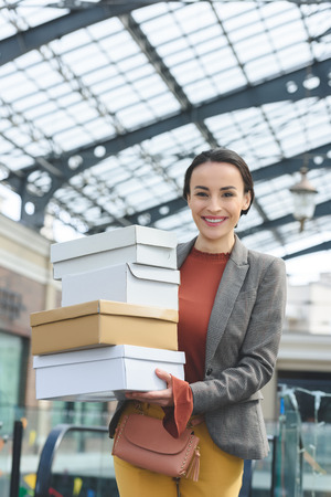 smiling attractive woman with shopping boxes looking at camera Banco de Imagens
