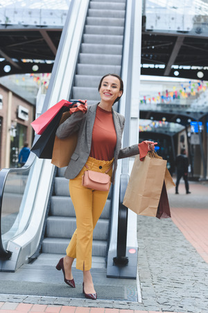 happy attractive woman walking with paper bags after shopping