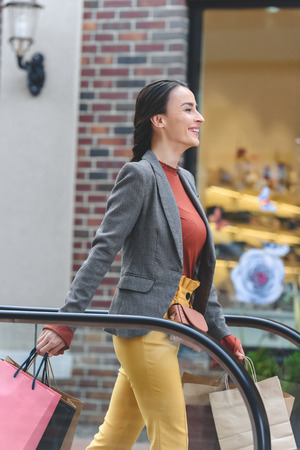 side view of attractive woman walking with shopping bags