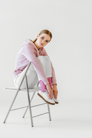 attractive young woman in pink hoodie sitting on chair on white