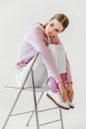 stylish young woman in pink hoodie sitting on chair on white