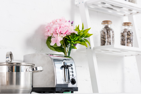 toaster, saucepan and pink flowers in kitchen