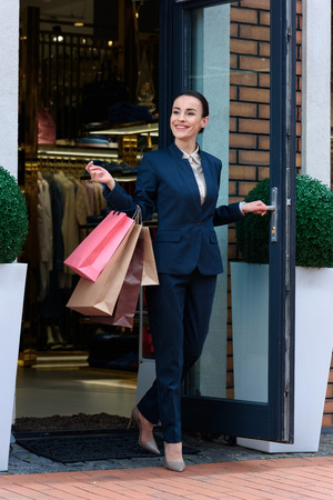 attractive businesswoman exiting store with shopping bags