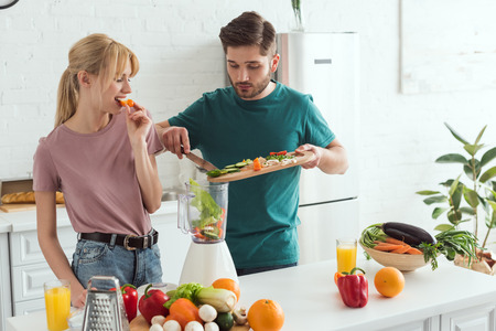 young couple of vegans preparing vegetable juice at kitchen
