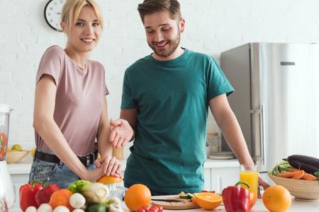 couple of vegans preparing juice with squeezer at kitchen Stockfoto