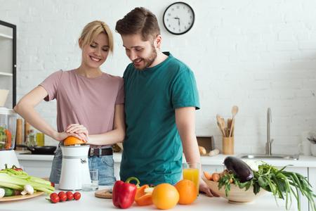 couple of vegans preparing fresh juice at kitchen Stockfoto
