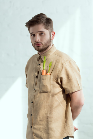 portrait of bearded man with fresh carrots in pocket, vegan lifestyle concept Imagens