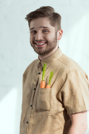 portrait of smiling bearded man with fresh carrots in pocket, vegan lifestyle concept