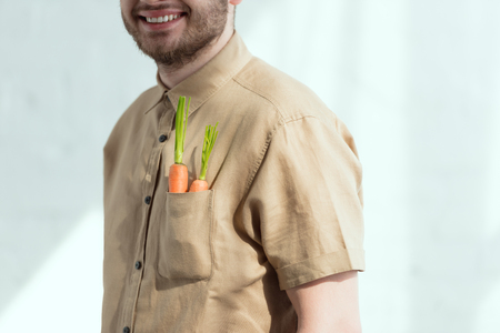 cropped shot of smiling bearded man with fresh carrots in pocket, vegan lifestyle concept Banco de Imagens