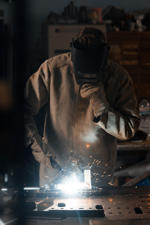 front view of welder in protection mask working with metal at factory Imagens