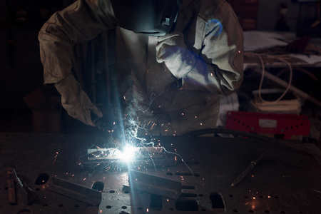 cropped image of welder in protection mask working with metal at factory Imagens
